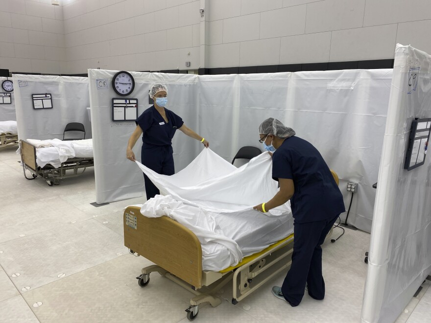 Hospital beds are set up in the practice facility at Sleep Train Arena in Sacramento, Calif. The facility is ready to receive patients as needed, as new coronavirus infections and deaths rise in the state.