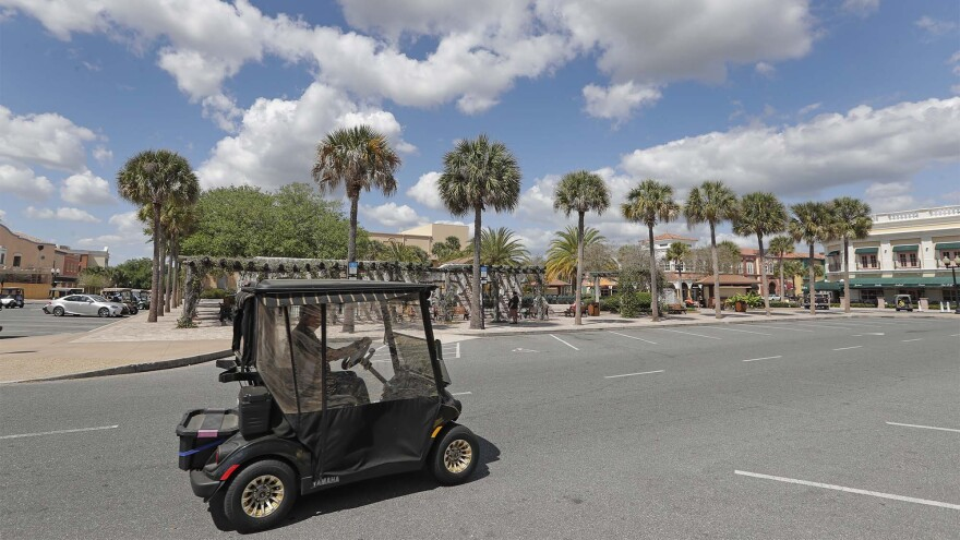A resident drives his golf card down what usually is a busy street in The Villages, Florida.
