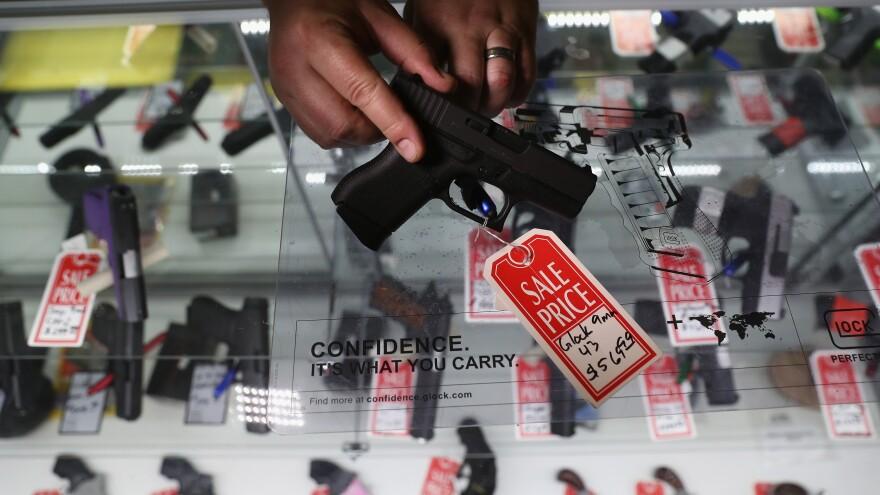 Gun shop owner Jeff Binkley displays a Glock 9mm pistol at Sarge's Sidearms in Benson, Ariz., in September.