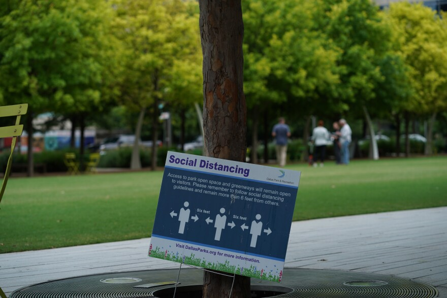 A sign in a park reminds visitors to maintain a distance of six feet from others.