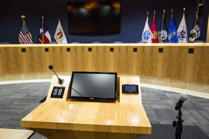 An empty city council dias with flags in the background.