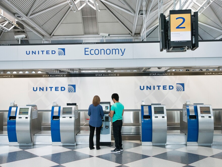 """Passengers check in for flights with United Airlines at Chicago O'Hare International Airport. United, American and Delta now offer no-frills """"basic economy"""" fares."""