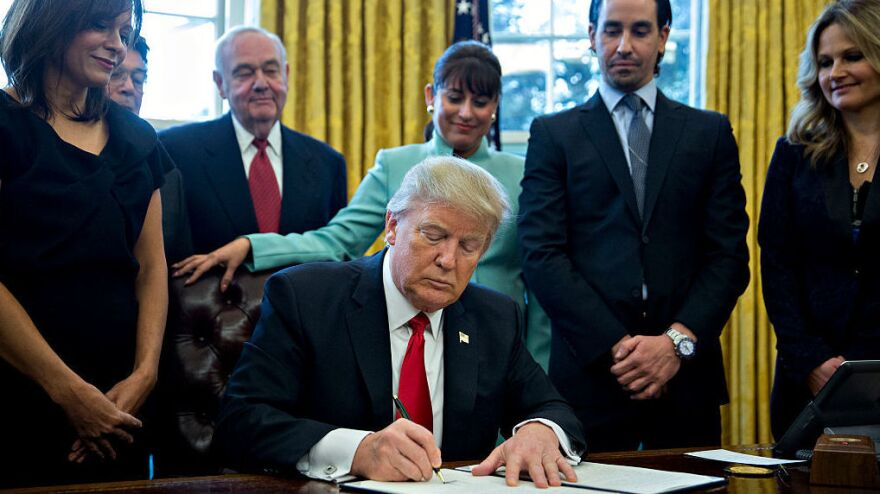 "President Trump signs an executive action in the Oval Office of the White House on Monday in Washington, D.C., saying he will ""dramatically"" reduce small business regulations overall."