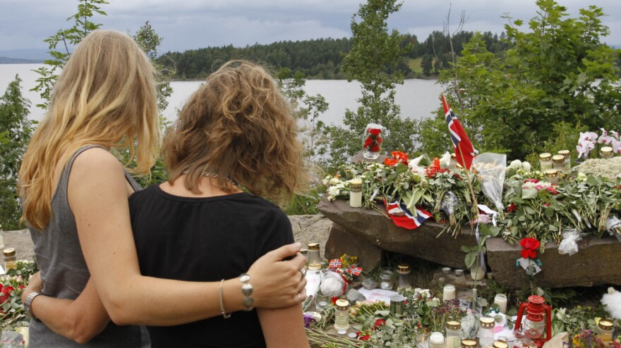 Two young women stand in silence after placing flower near Sundvollen close to the Utoya island, near Oslo, Norway, Tuesday, July 26, 2011, where a gunman Anders Behring Breivik killed at least 68 people.