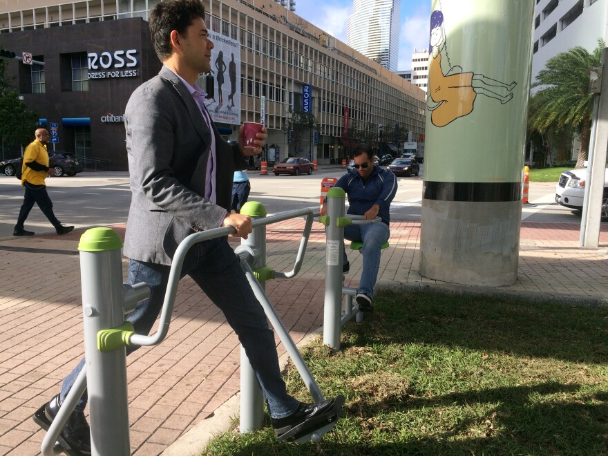 Coffee in hand, District 2 Commissioner Ken Russell tries out a piece of exercise equipment at the Biscayne Green installation. At right is Russell's chief of staff, Eleazar Melendez.