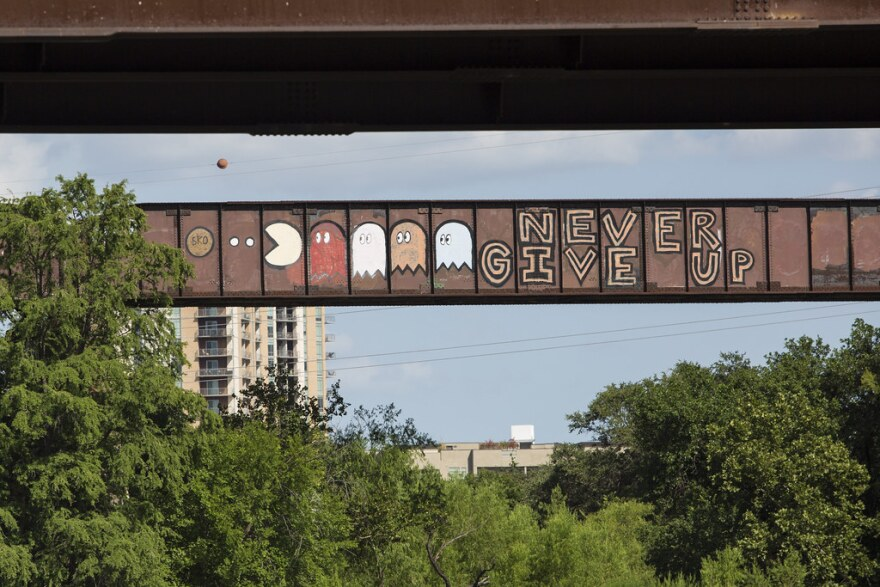 """The words """"Never Give Up"""" painted on the train bridge, with Pac-Man and four ghosts chasing him."""