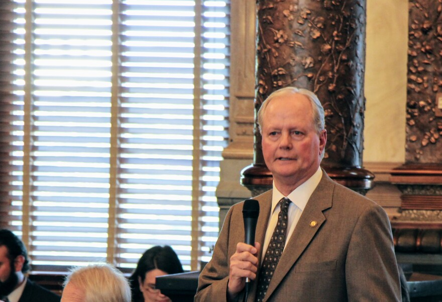 Gene Suellentrop holds a microphone on the floor of the Kansas Senate.