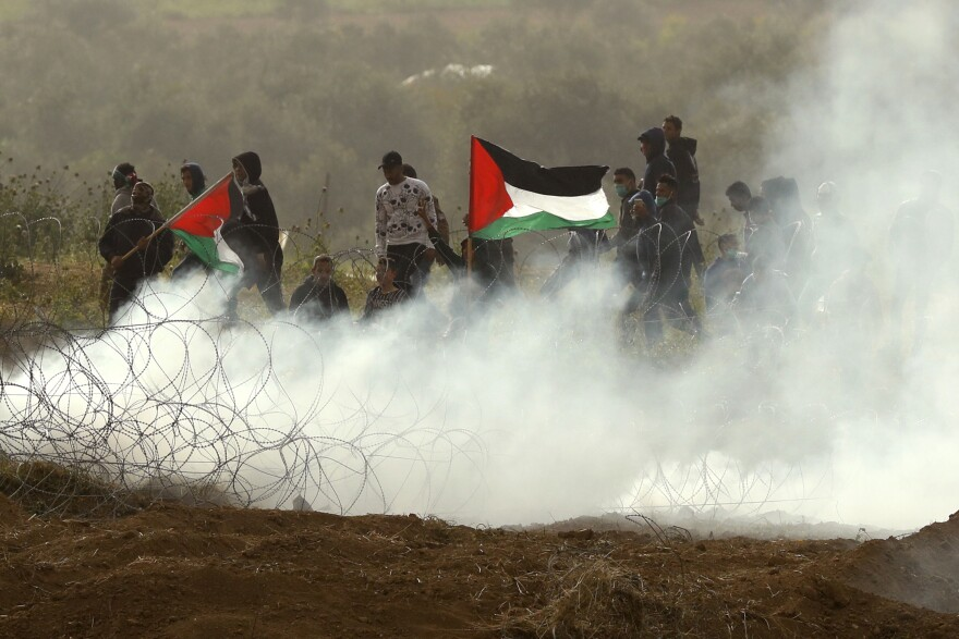 "Palestinian protesters wave national flags as they demonstrate to mark the first anniversary of the ""March of Return"" protests. Tens of thousands of Gazans gathered along the Israeli border to mark a year since protests and clashes erupted there, days ahead of an Israeli general election."