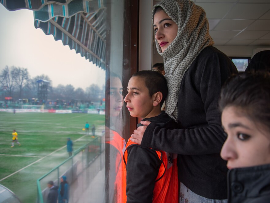 Mahak Farooq (center), 24, watches her brother Danish Farooq, who plays midfield for Real Kashmir, alongside 12-year-old Urooj Ayyub Bhat (left), a local boy who's one of the team's most loyal fans and a fixture at home games.