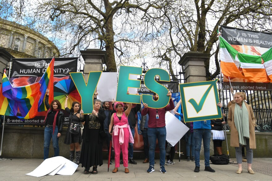 """""""Yes"""" vote campaigners cover abortion-rights opponents' posters with Irish and rainbow flags outside the Irish parliament in Dublin on May 4."""