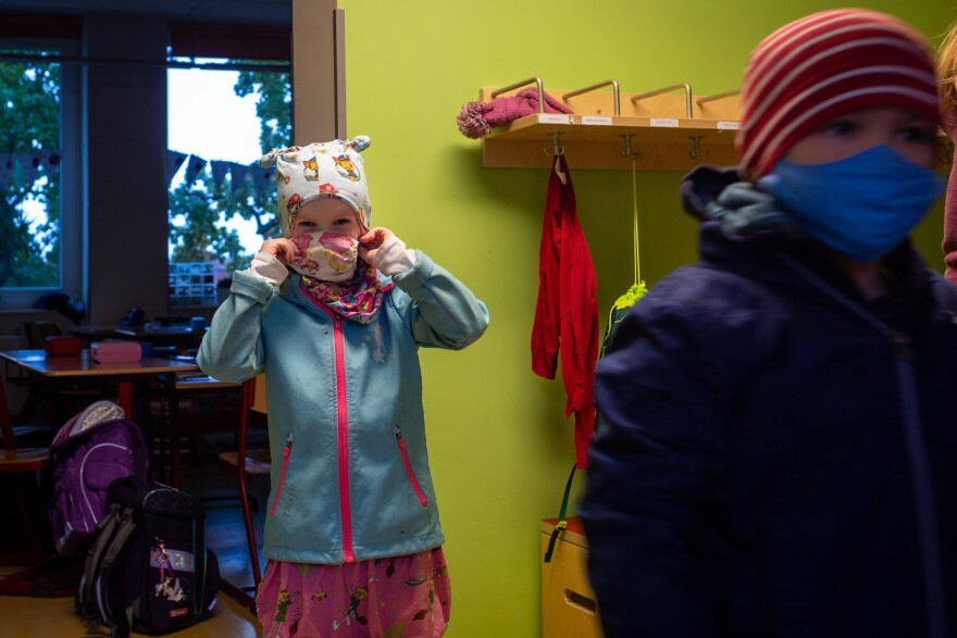 A young student dons a mask after putting on rain gear to go outside for recess at a primary school in Weimar, Germany, on Oct. 15, 2020. Students are only required to wear their masks when walking through hallways, though tighter measures could be put in place if coronavirus cases in Weimar increase.
