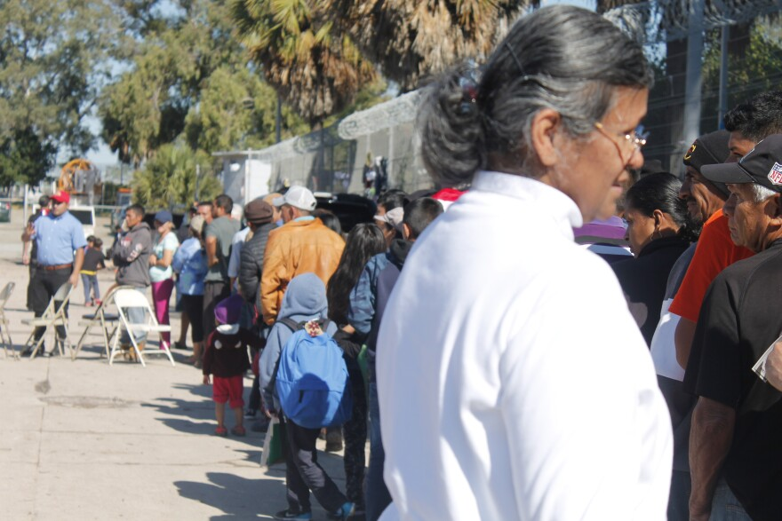 Hundreds of asylum seekers gather to receive tamales at a tent encampment in Matamoros, Mexico.