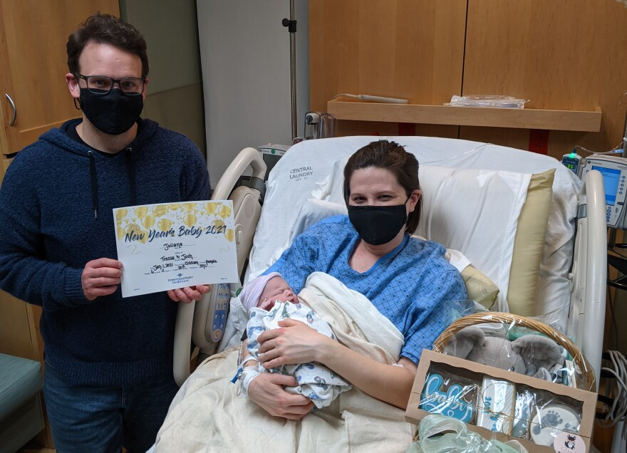 """A woman in a black mask in a hospital bed holds a new-born baby. A man in a mask stands beside the bed with a certificate that says """"New Year's Baby 2021."""""""