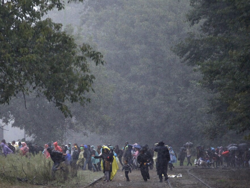 A group of migrants run to board a train as heavy rain starts to fall in Barcs, Hungary, on Thursday.