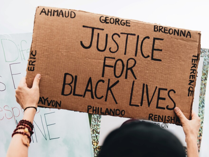 "A protester holds up a cardboard sign that reads, ""Justice For Black Lives,"" and lists the names Ahmaud, George, Breonna, Terrence, Renisha, Philando, Trayvon and Eric."
