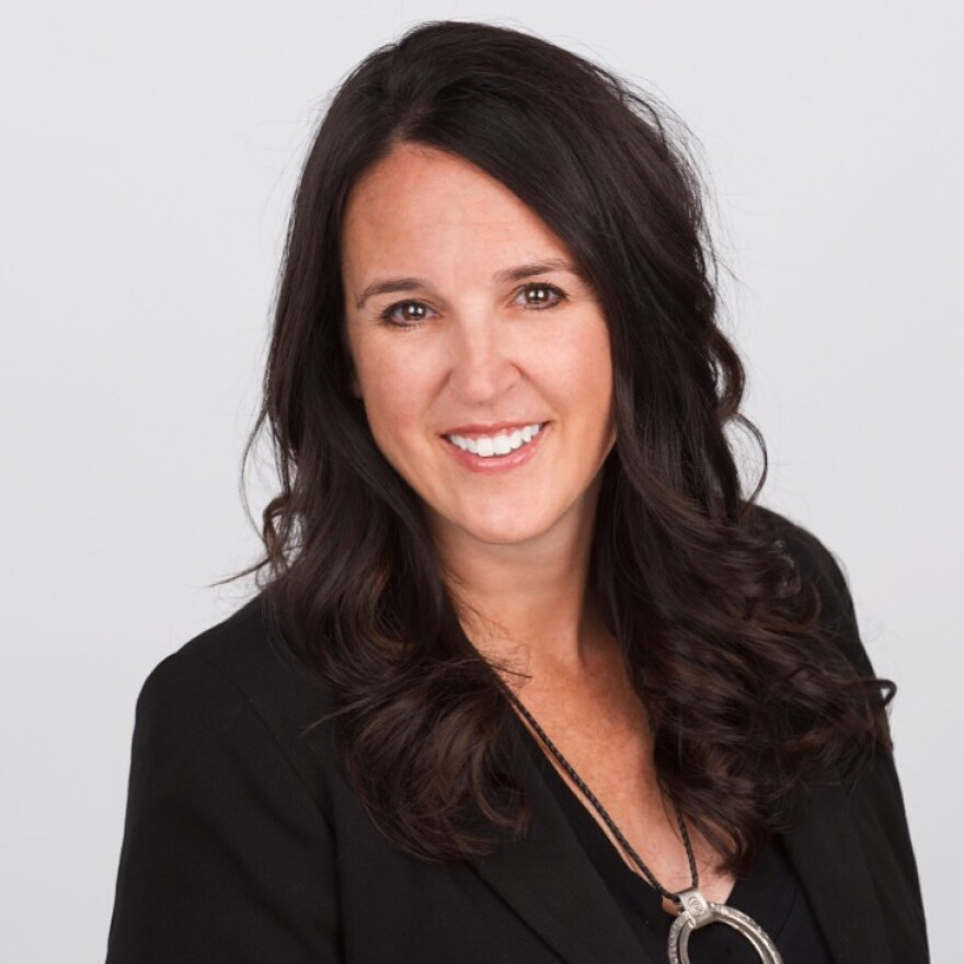 Professionally taken photo of a woman with long hair. She is wearing a blazer.