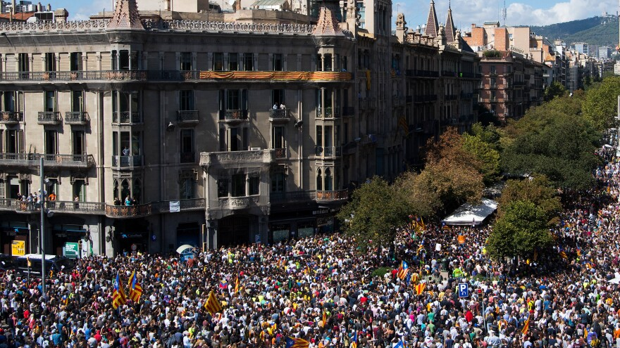 People demonstrate outside the Ministry of the Vice-presidency and of the Economy and Finance in Barcelona, Spain, as Spanish police officers conduct a search inside. Spanish Civil Guard police have stormed several Catalan government ministries in an attempt to stop the region's independence referendum on Oct. 1.