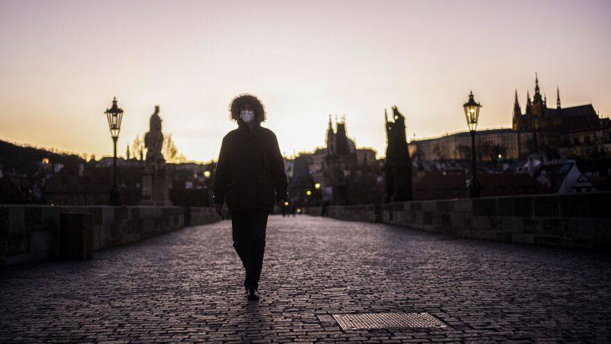 A man wearing a face mask crosses the Charles Bridge in Prague on Tuesday. The Czech Republic is one of a handful of places throughout Europe now mandating that residents wear face masks when they leave their homes.