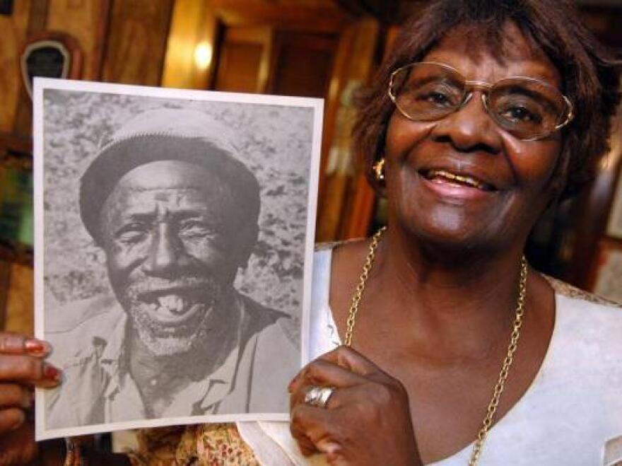 Martha McCullough shows off a photo of her grandfather, Christmas Moultrie, who was born on the Mulberry Grove Plantation before Gen. Sherman's army burned it down ahead of the capture of Savannah in 1864. Both McCullough and Hugh Golson, a descendant of the plantation's owner, knew Moultrie as children.