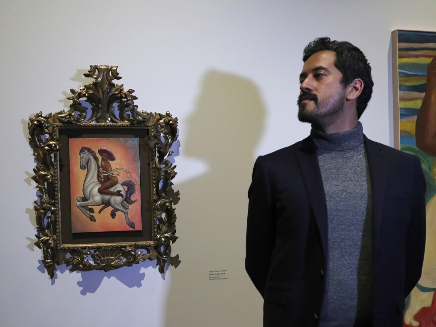 Mexican artist Fabián Cháirez stands next to his painting of Mexican revolutionary hero Emiliano Zapata, straddling a horse nude, wearing high heels and a pink hat, at the Fine Arts Palace in Mexico City on Dec. 11, 2019.