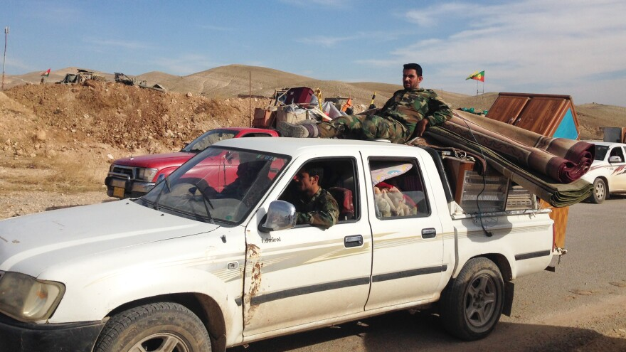 Trucks loaded with household appliances line up on their way out of Sinjar city. Iraqi Kurdish soldiers said they tried to stop people from leaving with suspected looted goods. But soon, the trucks outnumbered the soldiers and they let them through.