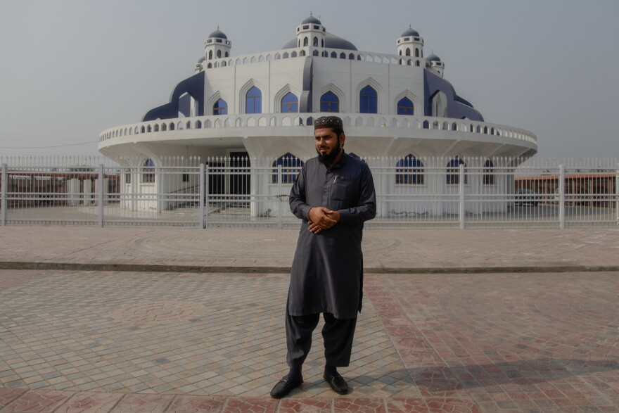 "Muhammad Saleem Asif stands in front of the mosque attached to the madrassa he runs in the village of Meer Muhammad. Seminaries ""bless the communities around them,"" he says."