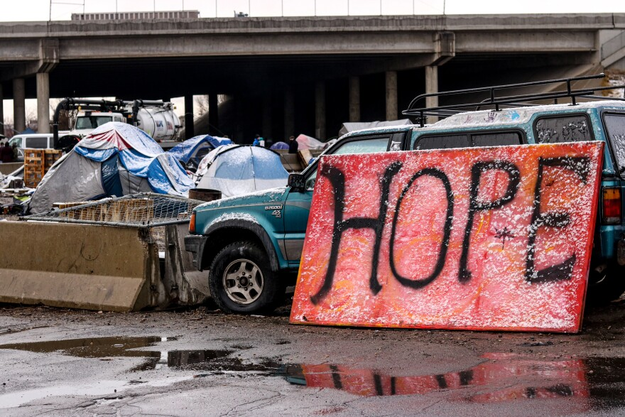 A photo of a homeless encampment with a red sign that reads 'Hope.'