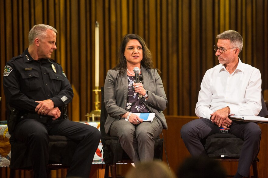 Austin Police Chief Brian Manley, left, and the Downtown Austin Alliance's Bill Brice listen to interim Homelessness Strategy Officer Veronica Briseño at the forum on Tuesday.