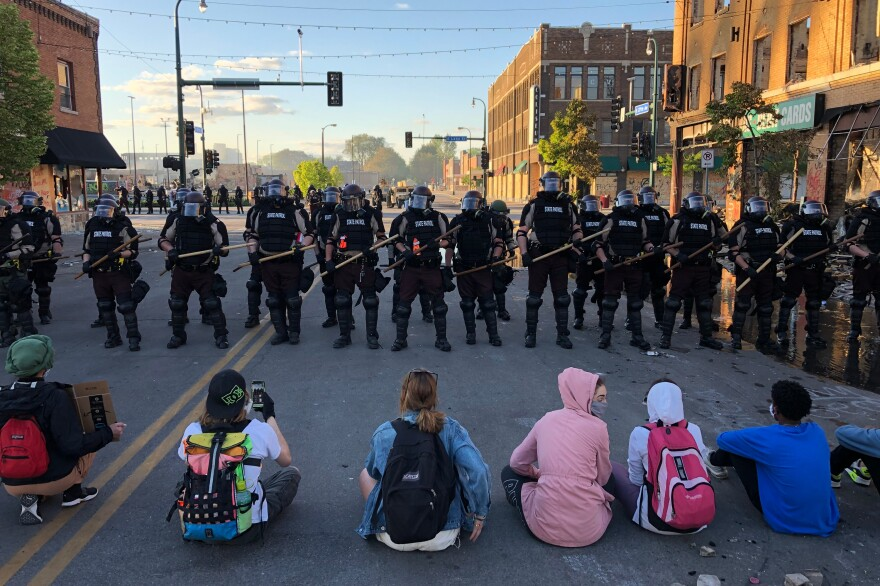 People sit on the street in front of a row of police officers during a rally in Minneapolis last year.