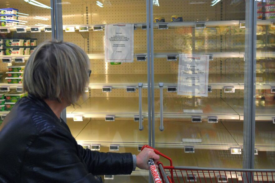 """A woman reads a sign that says, """"Due to a shortage of the raw material to make butter, we are not able to supply and sell you this product,"""" attached to an empty refrigerated supermarket shelf in western France."""
