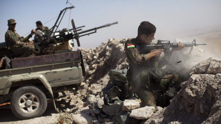 An Iraqi Kurdish peshmerga fighter fires at Islamic State militant positions from his position atop Mount Zardak east of Mosul, Iraq, on Sept. 9.