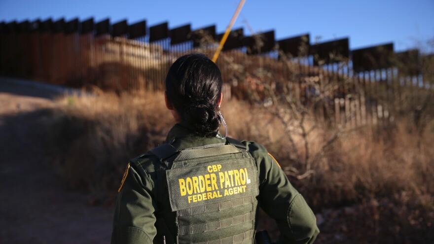 U.S. Border Patrol agent Nicole Ballistrea watches over the U.S.-Mexico border fence in Nogales, Ariz., in Dec. 2014.