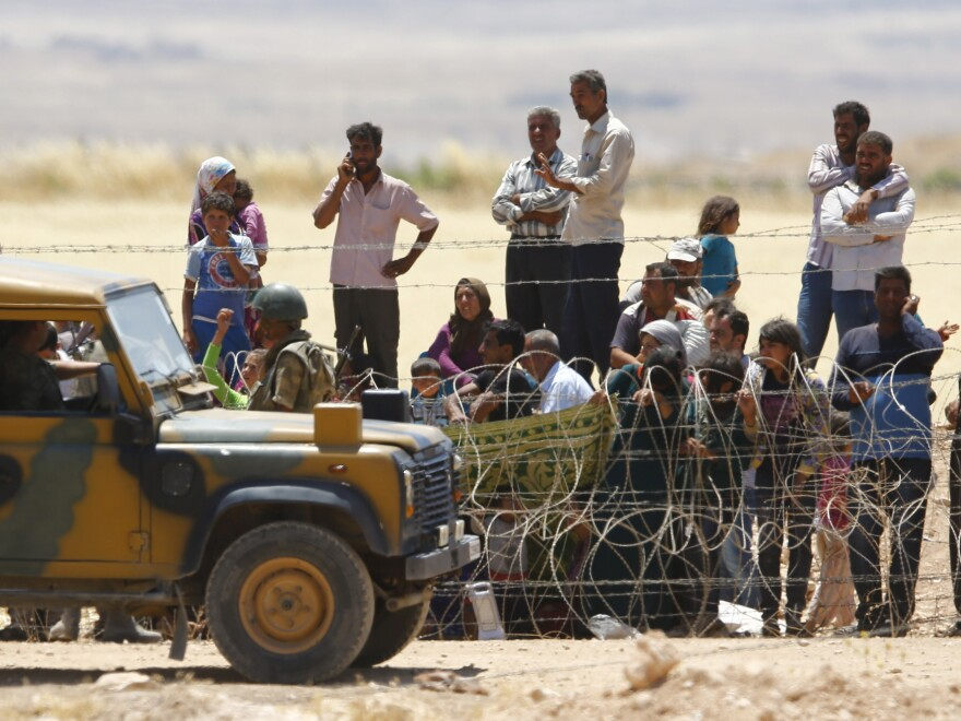 Syrian Kurds from Kobani wait behind the border fences to cross into Turkey on Friday. An attack by Islamic State fighters on the Syrian town of Kobani and a nearby village has so far killed at least 146 civilians, the second-biggest massacre by the hardline group in the country, a conflict monitor said on Friday.