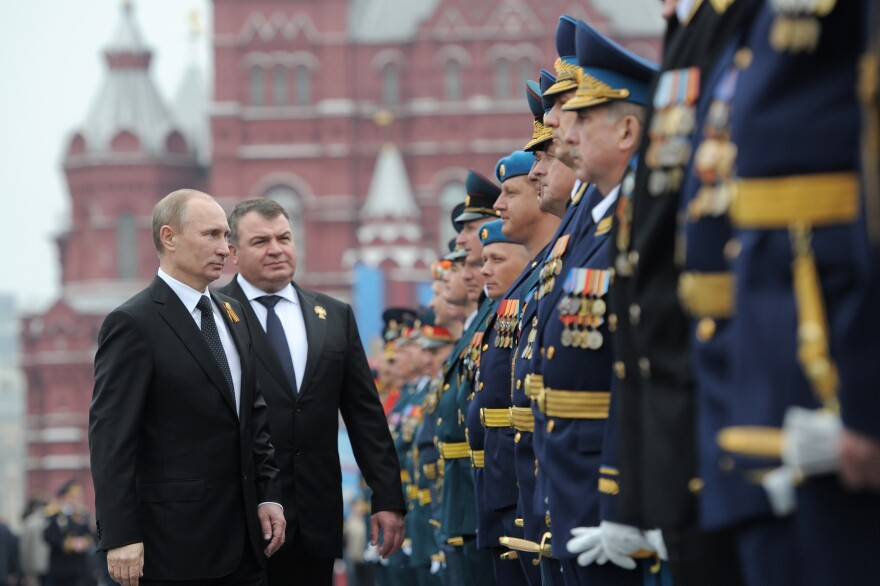 Russian President Vladimir Putin and former Defense Minister Anatoly Serdyukov, who was recently fired, review military officers on Moscow's Red Square in May. Putin's decision to sack Serdyukov has touched off widespread speculation on the motive.