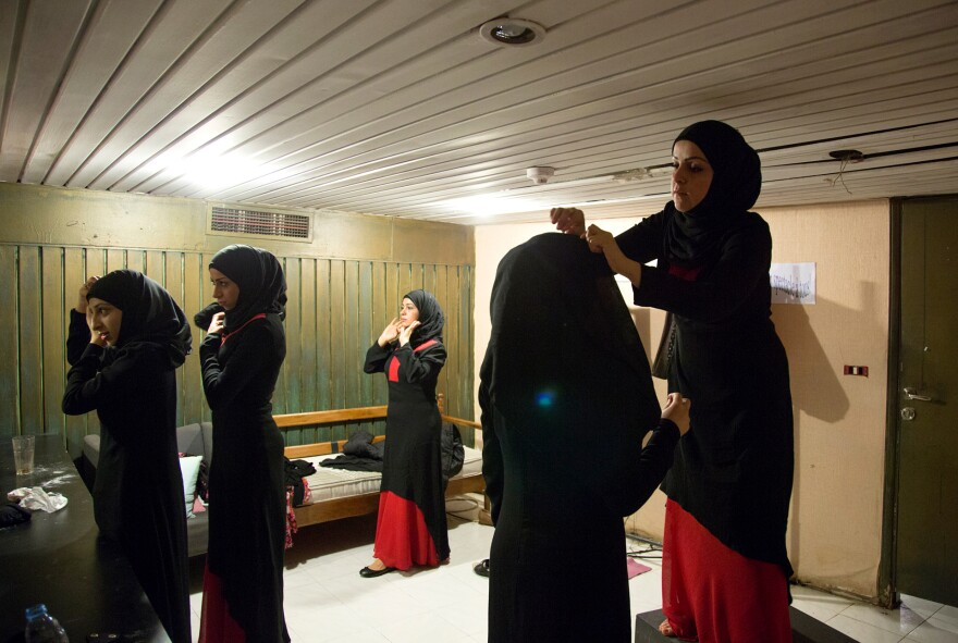 Syrian refugee women in Beirut, Lebanon, fix their veils in a dressing room before a rehearsal of an Arabic version of <em>Antigone</em>. The women are part of production that's been adapted to incorporate their experiences in an effort to help them heal.