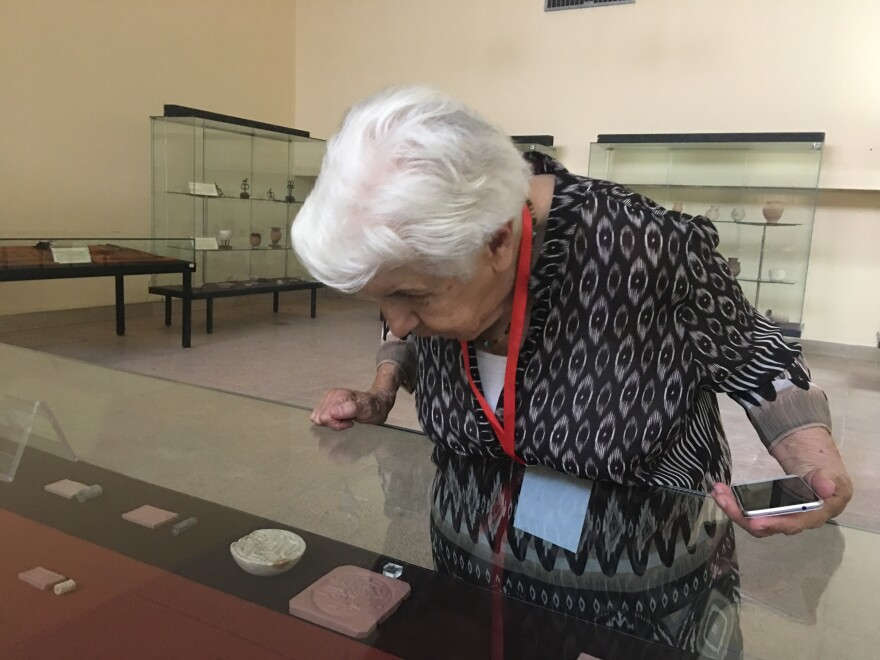 Gailani peers at ancient cylinder seals displayed at the national museum. She curated the original exhibit at the opening of the museum more than 50 years ago.