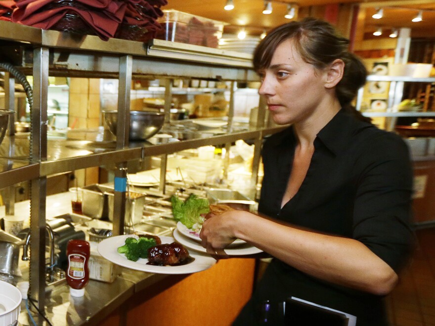 Seattle waitress Wendy Harrison picks up a lunch order on Monday. She stands to be affected by a $15 minimum wage approved by the Seattle City Council.