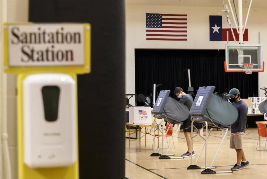 Voters voting while social distancing in a gym in Houston.