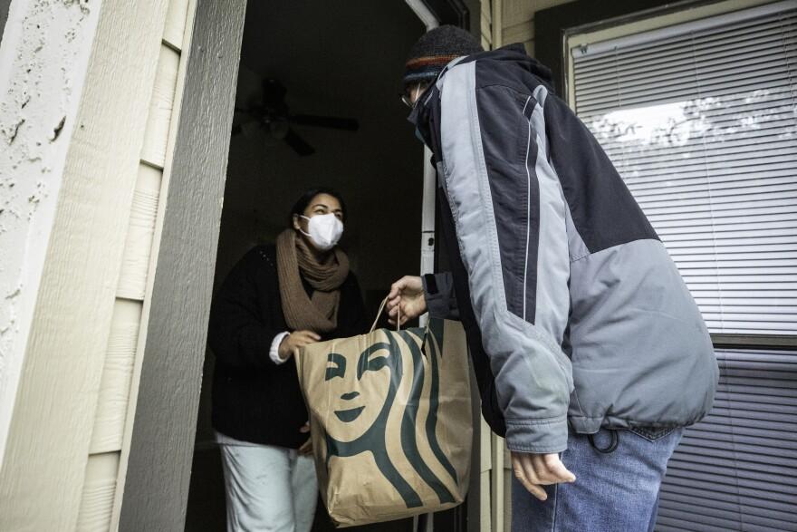 Hombre entrega bolsa de comida a una mujer
