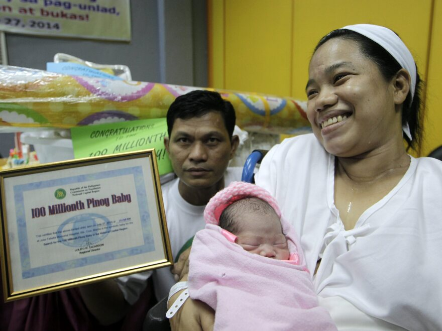 """Filipino Clemente Sentino Jr (L), 45 and Dailin Cabigayan (R), 27 holds their 6 lbs newborn baby girl marking the """"100 million population of the Philippines."""""""