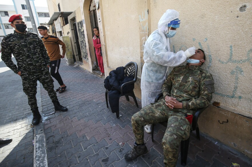 A Palestinian medical worker takes a swab sample from security personnel guarding the homes of quarantined patients infected with the COVID-19 coronavirus in Rafah, in the southern Gaza Strip in January.