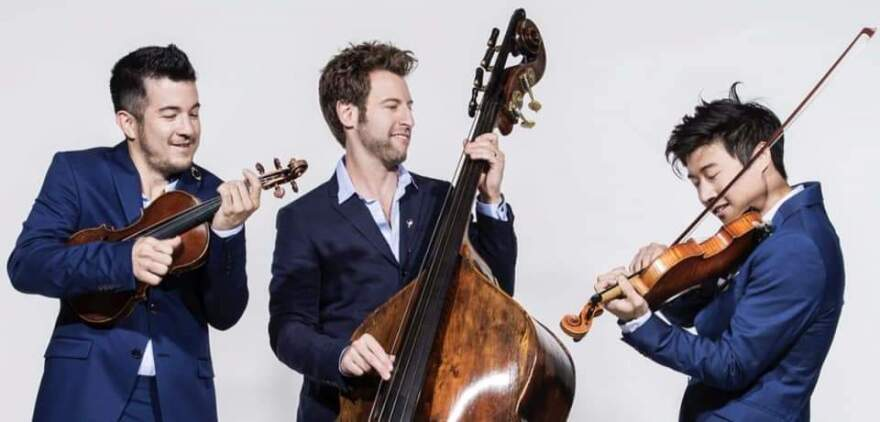 Three men in blue suits playing instruments