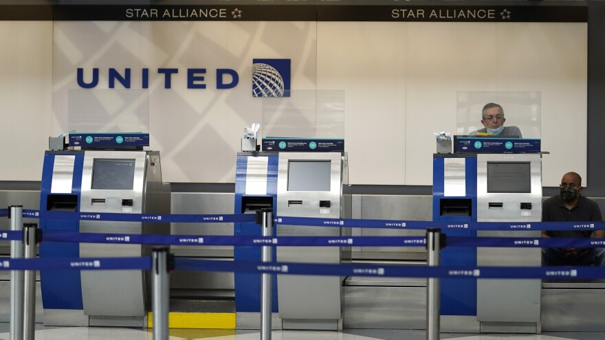 United Airlines employees work at ticket counters at Chicago's O'Hare International Airport on Oct. 14, 2020. United and other airline stocks have been hard hit by the pandemic economic slowdown.