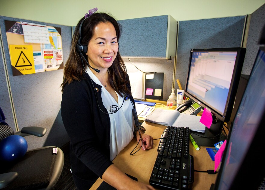 Clinical Contact Center employee Ruth Banilbo stands at her work station with a headset on for answering calls