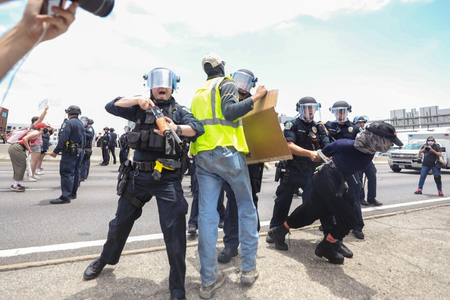 Austin Police officers take at least one protester into custody on Interstate 35 Saturday afternoon.