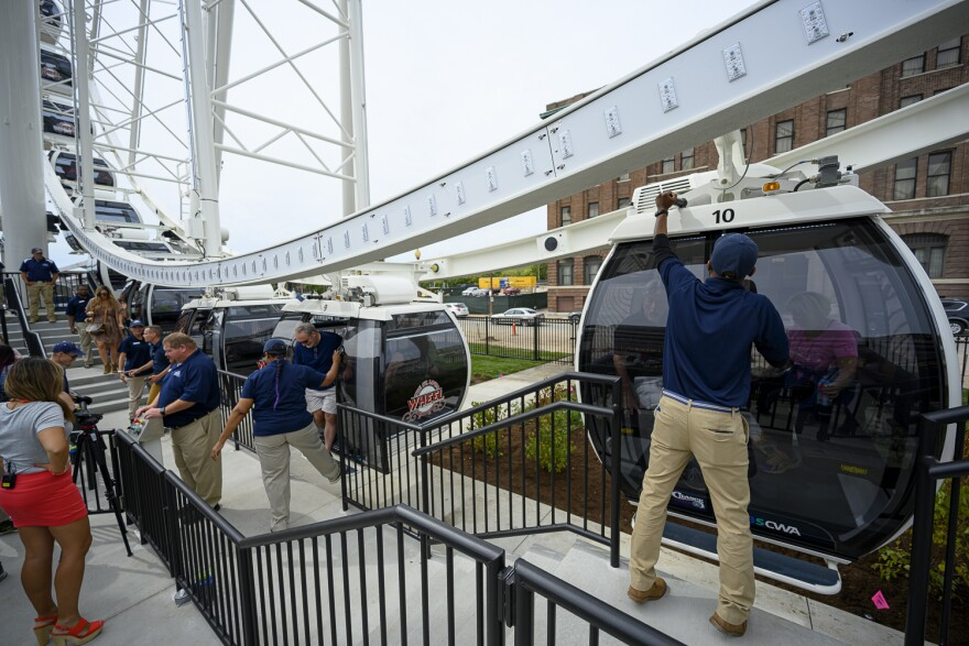 Attendants help riders board the St. Louis Wheel during a media preview event on Sept. 24, 2019. The attraction opens to the public September 20.