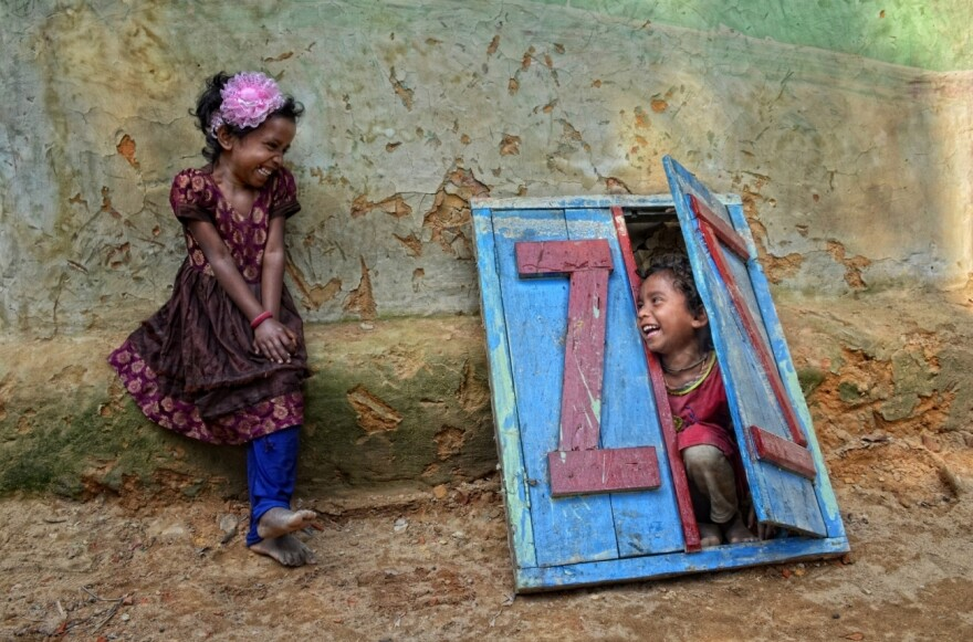 Two girls play in front of a house in Sylhet, Bangladesh.