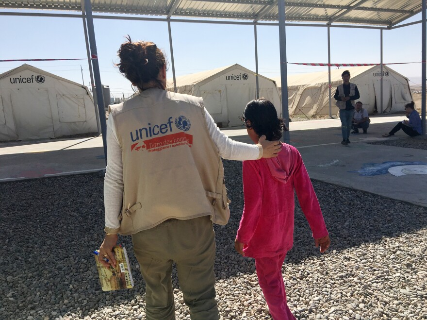 """Kawkab walks with a social worker in the Dabaga camp for displaced Iraqis. Kawkab says she was seven or eight when she saw ISIS militants shoot her mother dead. """"They shot her with an assault rifle,"""" she says. """"They shot her and she died and they threw her off the bridge. I asked them, 'Why did you kill her? She's my mother. She didn't do anything.'"""""""