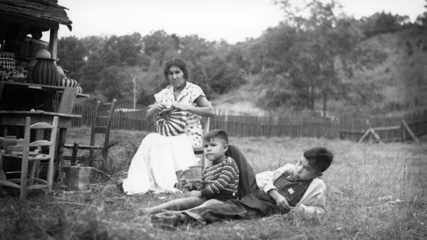 Archival image of woman weaving basket and two children.
