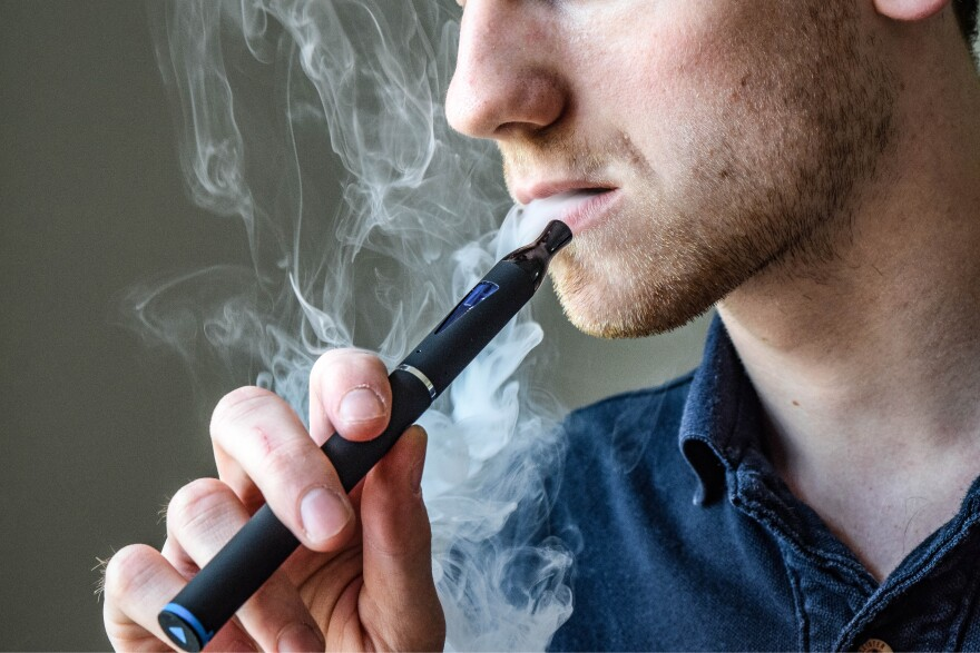 A man puffs out vapor from an e-cigarette.